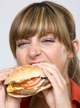 Marie Claire health news: Woman eating a burger