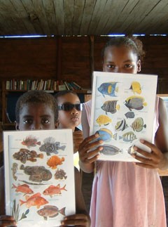 3 children holding fish charts in Madagascar