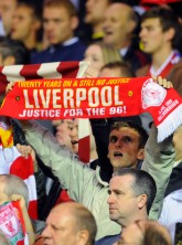 Liverpool fan holds up a justice for the 96 banner
