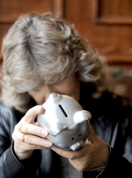 Retired woman using piggy bank