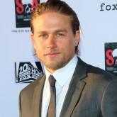 Charlie Hunnam wears a grey suit on the red carpet
