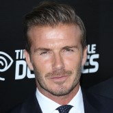 David beckham smoulders in a black suit jacket, white shirt and tie