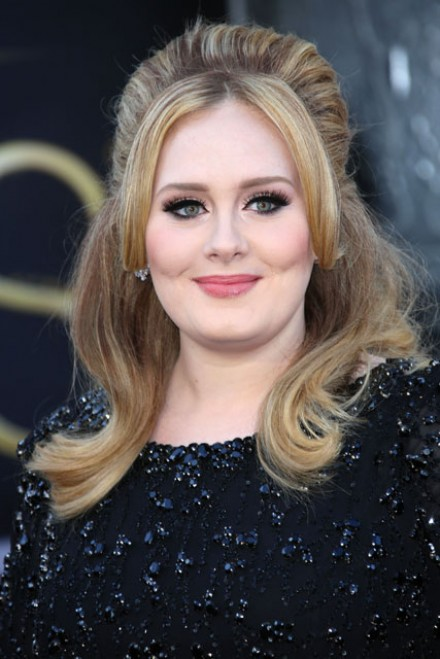 Adele with her hair worn loose and a sAdele in a black sequin dress with high volume hairtatement red lip on Oscars night