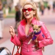 Reese Witherspoon as Elle Woods in Legally Blonde in a leather pink suit and her dog